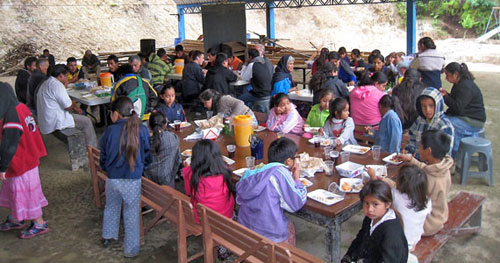 Children and adults gathered around tables eating