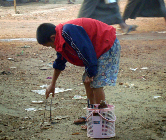 burmese orphan picking up trash